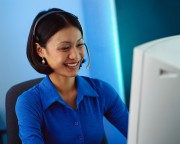 Businesswoman Wearing Headset at Computer